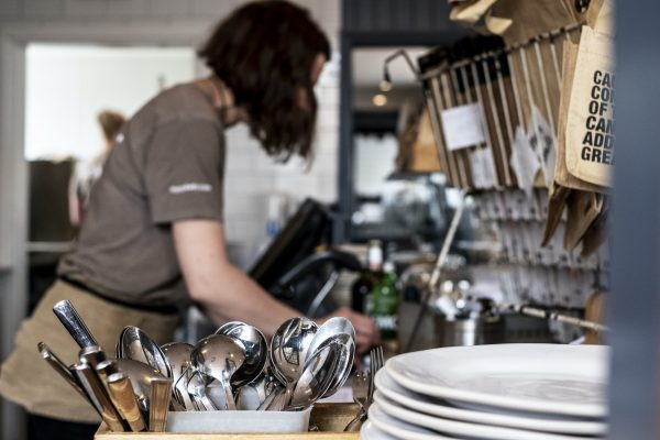 Close up of stack of plates and container with cutlery in a restaurant, woman working in background.